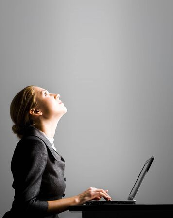 looking upwards: Photo of pretty secretary typing and looking upwards at workplace Stock Photo