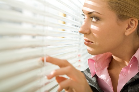 Image of pretty businesswoman looking through venetian blind in office photo