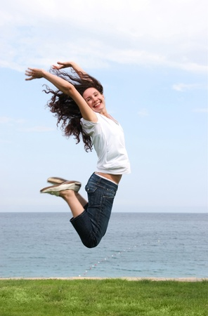 Joyful female in high jump over green grassland with blue sea and sky at background