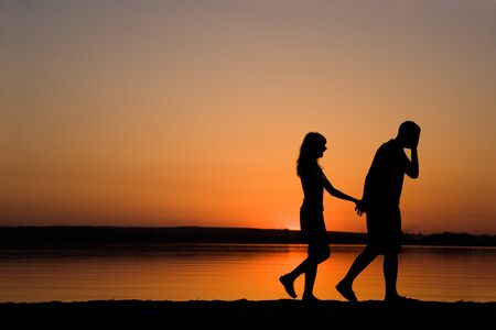 Silhouettes of man and woman holding each other by hands while walking at sunset photo