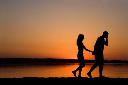 parejas caminando: Siluetas de hombre y mujer sosteniendo entre s� por manos mientras caminaba al atardecer Foto de archivo