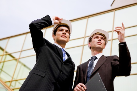 from below: Photo of two co-workers discussing work while one of them showing something to colleague Stock Photo