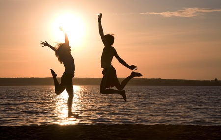 Silhouettes of happy couple jumping on background of lake at sunset photo