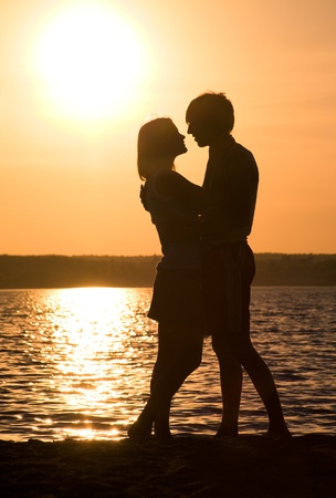 Profiles of romantic couple embracing each other on background of lake at sunset Stock Photo