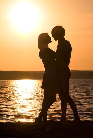couple enlac�: Profils de couple romantique embrassant mutuellement sur le fond du lac au coucher du soleil