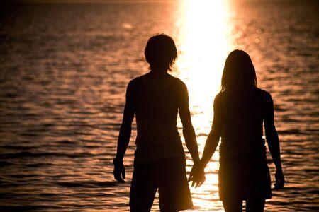 femme romantique: Profils des couples romantiques se tenant par les mains et en admirant le lac au coucher du soleil