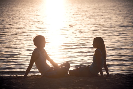 male silhouette: Photo of serene couple sitting on the seashore and talking at sunset Stock Photo