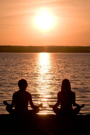 Meditating couple sitting in pose of lotus during wonderful sunset photo