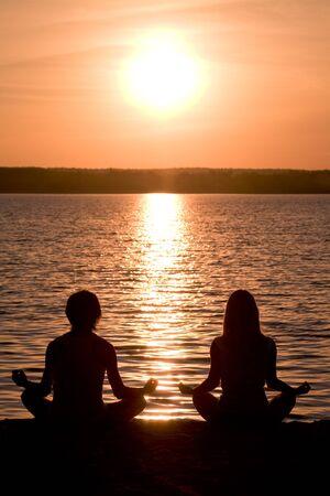 yoga sunset: Meditating couple sitting in pose of lotus during wonderful sunset