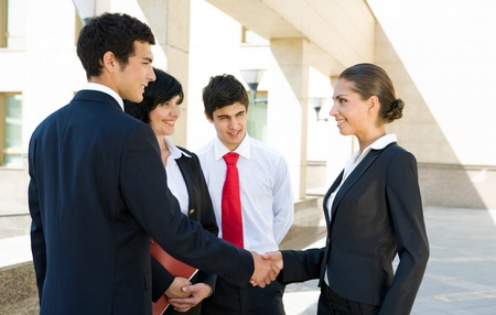 Photo of successful associates handshaking after striking deal outdoors at meeting photo