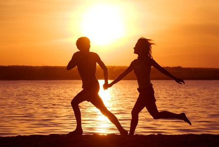 Silhouettes of happy couple running down seashore at sunset photo