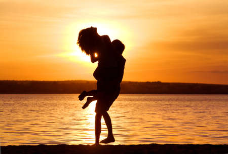 Silhouettes of happy guy holding his girlfriend by the lake at sunset photo