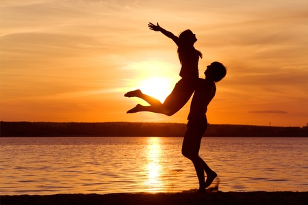 Figures of happy guy holding his girlfriend while the latter raising her arms at sunset