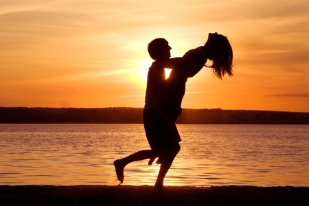 Silhouettes of happy guy holding his girlfriend and having fun at sunset photo