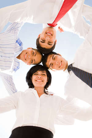 Below view of several successful partners embracing and looking at camera with smiles Stock Photo - 8441372