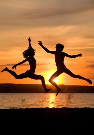 Silhouettes of happy couple jumping over seashore at sunset photo