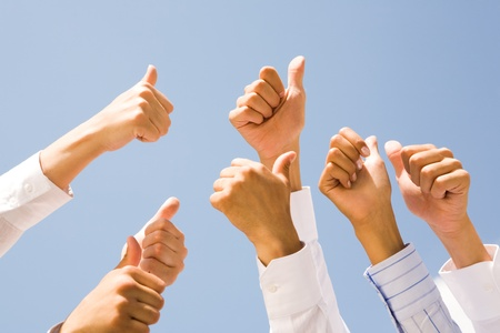 thumbs up gesture: Image of several human hands showing thumbs up against clear blue sky