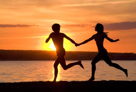 happiness people silhouette on the sunset: Outlines of happy guy and girl running down seashore at sunset Stock Photo