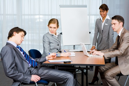 sternly: Photo of businesspeople looking sternly at their sleeping colleague at presentation