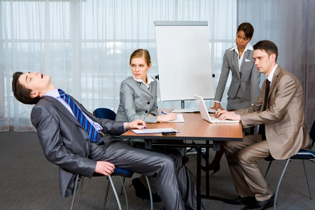 sternly: Photo of displeased businesspeople looking sternly at snoring man at presentation
