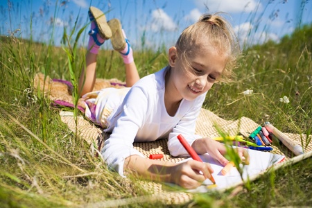 Portrait of cute girl with fair hair lying on grassland and drawing Stock Photo - 8450330