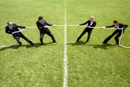 Businessmen and businesswomen playing tug of war photo