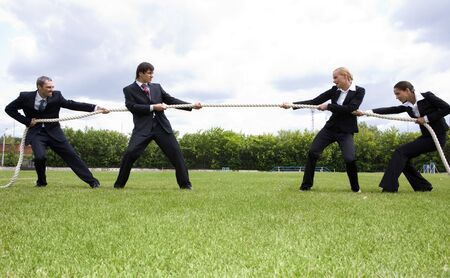 tug: Photo of business people stretching the rope in the stadium