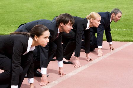 compete: Confident business people lined up getting ready for race