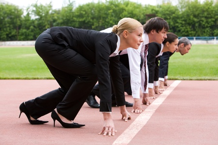 compete: Row of business people getting ready for race Stock Photo