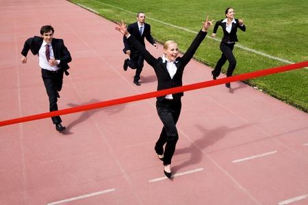team winner: Image of joyful businesswoman winning a business race