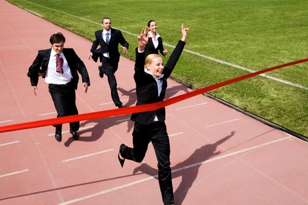 Photo of happy businesswoman crossing finish line during race  photo