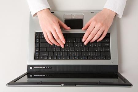 Visualizzare di sopra delle Belle mani femminile facendo il lavoro al computer