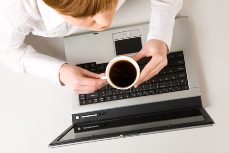 Photo of woman holding cup of coffee at workplace  photo