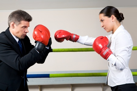 Portrait of aggressive businessman in boxing gloves with serious female opposite him photo