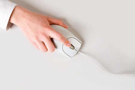 Woman�s hand touching computer mouse placed on white table  photo