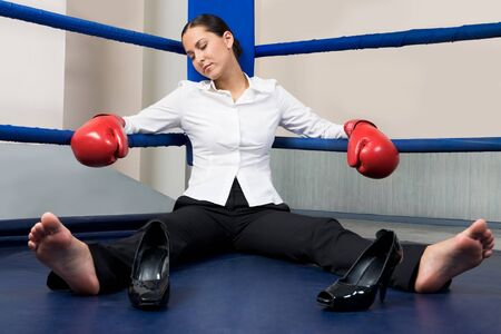 Portrait of tired businesswoman in boxing gloves sleeping on boxing ring photo