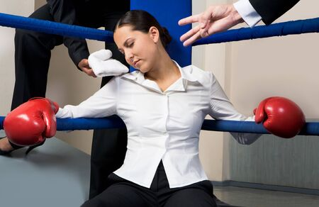 tiresome: Portrait of tired businesswoman in boxing gloves sleeping on boxing ring after hard game Stock Photo