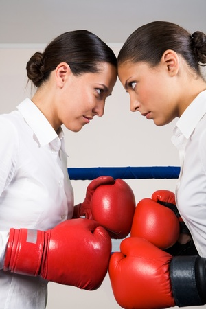 Photo of aggressive business women in boxing gloves fighting with each other photo