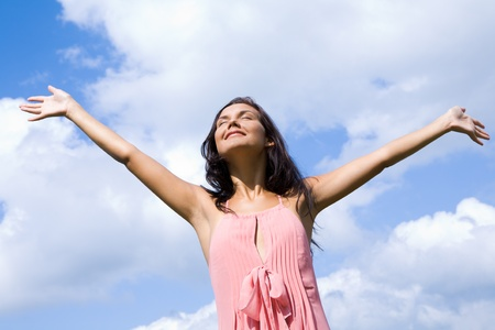 grateful: Portrait of happy girl praising God with her eyes shut and raised arms on background of cloudy sky Stock Photo