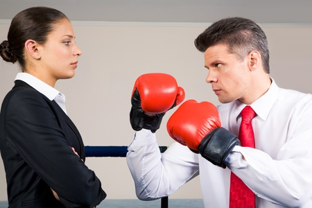 Portrait of aggressive businessman in boxing gloves fighting with serious crossed armed female  photo
