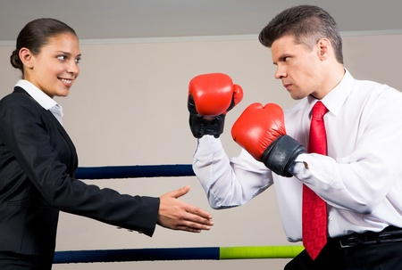 Portrait of aggressive businessman in boxing gloves fighting with positive female with her arm stretched for handshake photo