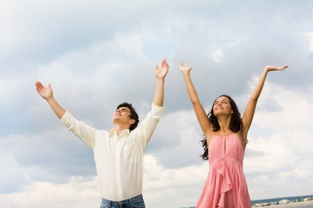 praising: Portrait of happy couple standing with raised arms on background of cloudy sky
