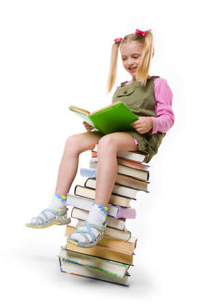 Cute girl sitting on the heap of books and reading one of them over white background photo