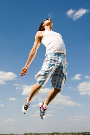 Image of energetic man jumping high against bright blue sky