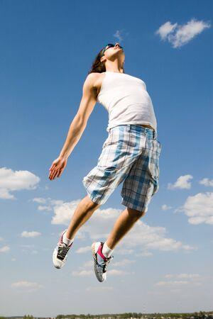 Immagine di uomo energico, salto in alto contro il cielo blu brillante