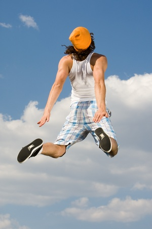Rear view of energetic guy jumping high against bright blue sky photo
