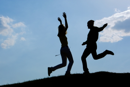 Image of cheerful girl and guy moving energetically against bright blue sky outdoors photo
