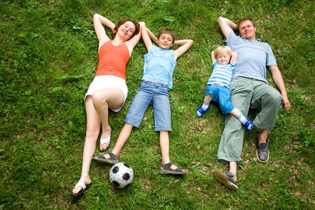 Image of four people lying on the grass together  Stock Photo - 8448459