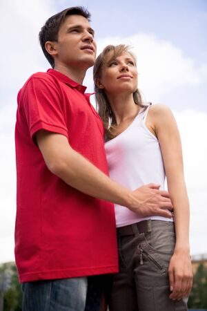 Photo of happy couple looking aside during spending time outdoors photo
