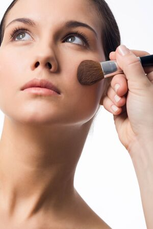 Fresh girl having makeup procedure over white background photo